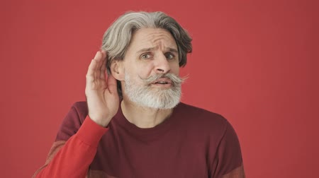 malentendu : An elderly gray-haired bearded man in a red sweater trying to listen the voice while putting his hand to his ear isolated over red wall Vidéos Libres De Droits