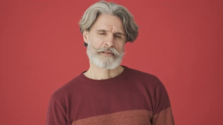 cavalheiro : Concentrated gray-haired bearded man in a red sweater listening then showing a negative gesture while shaking his raised finger isolated over red wall