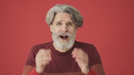 cavalheiro : Shocked discouraged elderly gray-haired man in a red sweater putting his hands to his head and screaming isolated over red wall Stock Footage