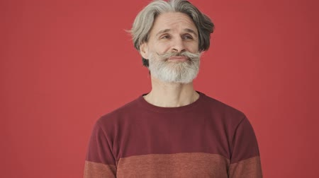 케케 묵은 : Bored gray-haired bearded man in a red sweater looking around isolated over red wall 무비클립