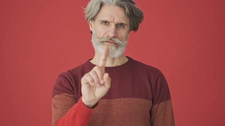 серый фон : An old displeased gray-haired bearded man in red sweater shaking his raised finger negatively isolated over red wall