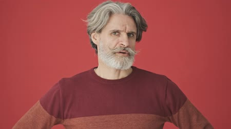 cavalheiro : Serious displeased gray-haired bearded man in red sweater shaking his head negatively isolated over red wall Stock Footage