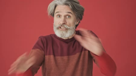 sem camisa : Serious elder gray-haired bearded man in red sweater crossed his hands while making a negative gesture isolated over red wall