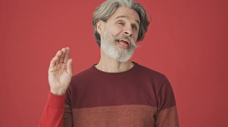 gebreid : Displeased elder gray-haired bearded man in red sweater showing a boring gesture with open mouth and facial expressions isolated over red wall