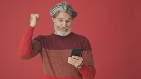 knitted : Attractive elder gray-haired bearded man in the red sweater doing a winner gesture while holding a smartphone isolated over red wall
