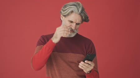 deprivation : Upset disappointed elder gray-haired bearded man in the red sweater touching his head while holding a smartphone isolated over red wall Stock Footage
