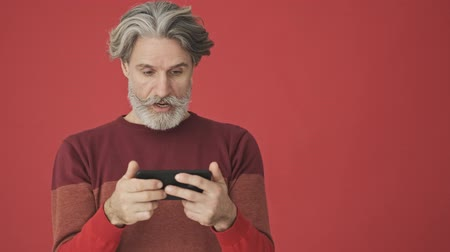 серый фон : Surprising elder gray-haired bearded man in the red sweater using a smartphone horizontally isolated over red wall