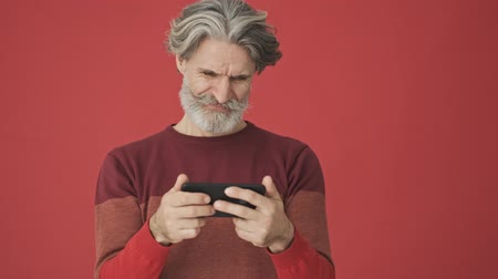 puzzled : Displeased bored gray-haired bearded man in the red sweater using a smartphone horizontally isolated over red wall Stock Footage