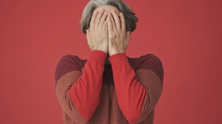скрывать : Frighten shocked gray-haired bearded man in the red is covering his face with his hands isolated over red wall Стоковые видеозаписи