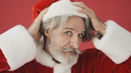 cavalheiro : Handsome gray-haired bearded man in Santa Claus costume correcting his red hat then smiles tot the camera isolated over the red background in studio Stock Footage