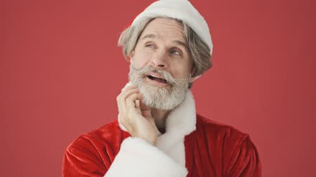 серый фон : Pensive positive gray-haired bearded man in Santa Claus costume thinking about something while touching his chin isolated over the red background in studio