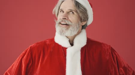 tur : Happy dreaming gray-haired bearded man in Santa Claus costume looking to the side with a smile isolated over the red background in studio