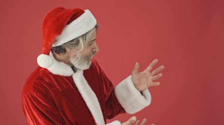 świety mikołaj : Attractive gray-haired bearded man in Santa Claus costume looking to the side and showing something with his empty hands isolated over the red background in studio