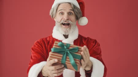 серый фон : Happy elderly gray-haired bearded man in Santa Claus costume is presenting a gift to the camera isolated over the red background in studio