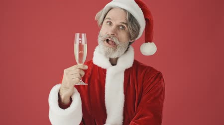 świety mikołaj : Joyful elderly gray-haired bearded man in Santa Claus costume is holding a glass of champagne while winking to the camera isolated over the red background in studio