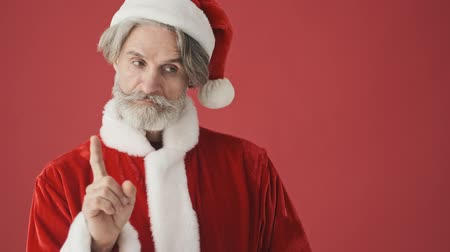 świety mikołaj : An elderly gray-haired bearded man in Santa Claus costume is making a choice while pointing with a finger isolated over the red background in studio Wideo