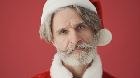 nem emberek : Cropped view of a serious elderly gray-haired bearded man in Santa Claus costume is shaking his head negatively isolated over the red background in studio