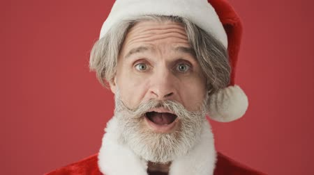 evet : Cropped view of a happy positive elderly gray-haired bearded man in Santa Claus costume is looking to the camera while agreeing with something isolated over the red background in studio
