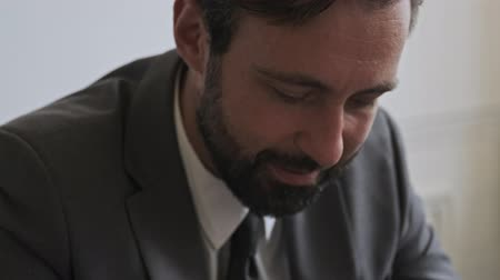 korporacja : Close up view of Smiling handsome bearded businessman working at office
