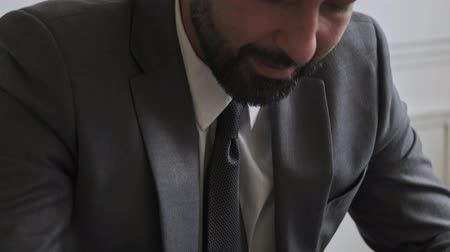 dyrektor : Close up view of Smiling concentrated handsome bearded businessman working at office Wideo