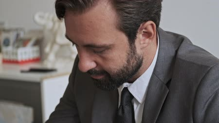 dyrektor : Close up view of Concentrated handsome bearded businessman writing something at office