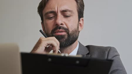 небритый : Concentrated handsome bearded businessman reading something at office Стоковые видеозаписи