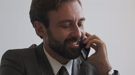 gadżety : Close up view of happy handsome bearded businessman talking by smartphone while sitting at office