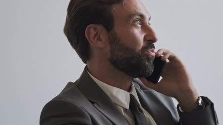 gadżety : Close up view of smiling handsome bearded businessman talking by smartphone while sitting at office