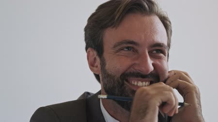 dyrektor : Close up view of Laughing handsome bearded businessman talking by smartphone while sitting at office