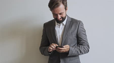 dyrektor : Happy handsome bearded businessman using smartphone while standing near the wall at office Wideo