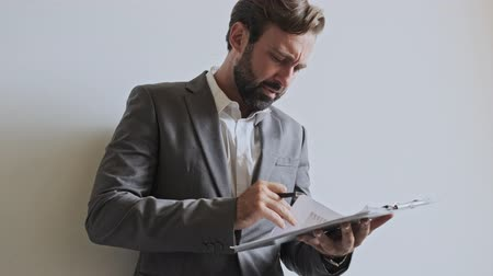 korporacja : Displeased handsome bearded businessman checking something in clipboard and doesn�t finding something while standing near the wall at office Wideo