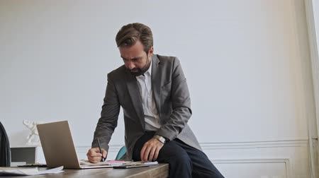 directeur : Serious handsome bearded businessman using laptop computer and writing something while sitting on the table at office Vidéos Libres De Droits