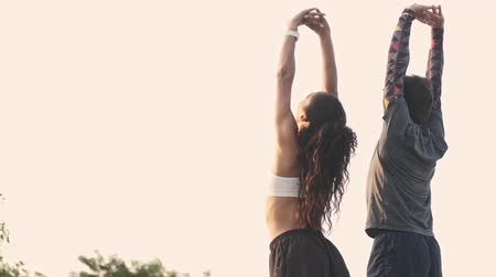 emelt : Back view of strong couple in sportswear stretching their backs together while making their hands raised at playground outdoors