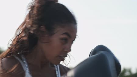 тонкий : Cropped view of african american woman in black boxing gloves training at playground outdoors