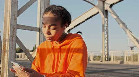 incecik : Beautiful peaceful african american woman wearing orange hoodie using her smartphone and earbuds while sitting on the old bridge