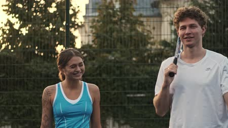 tribunal : Cheerful curly male tennis player holding tennis racket and walking with his happy female opponent on tennis court