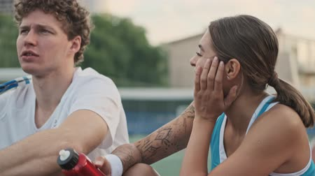 feliz : Carefree happy curly male tennis player talking and having rest together with his happy female opponent on tennis court Stock Footage
