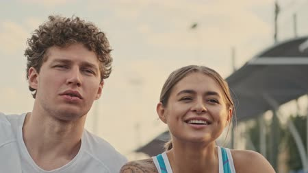 opponent : Close up view of Carefree pleased curly male tennis player looking away and having rest together with his happy female opponent on tennis court Stock Footage