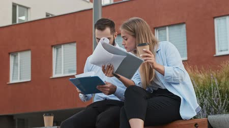 concentrar : Calm young office colleagues checking something in clipboards while sitting on bench outdoors