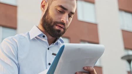 chemise à carreaux : Close up view of Concentrated pensive bearded businessman holding clipboard and writing something outdoors Vidéos Libres De Droits