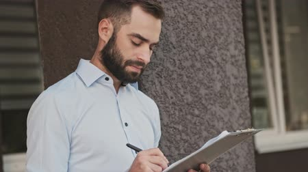 yöneticiler : Side view of serious pensive bearded businessman writing something in clipboard outdoors