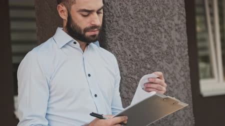 barbu : Serious bearded businessman checking and reading something in clipboard outdoors