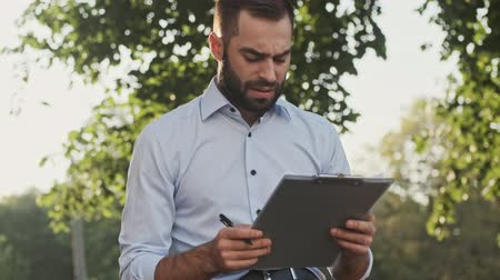 chemise à carreaux : Serious bearded businessman checking something in clipboard and becoming unhappy while sitting in park outdoors Vidéos Libres De Droits