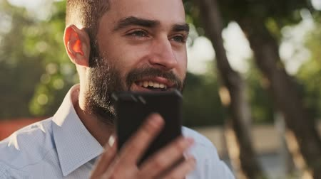 formální zahrada : Close up view of Happy bearded businessman answering the call and talking by smartphone while sitting in park outdoors