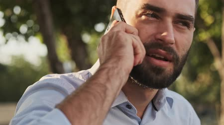 formální zahrada : Close up view of pleased bearded businessman talking by smartphone and looking around while sitting in park outdoors Dostupné videozáznamy