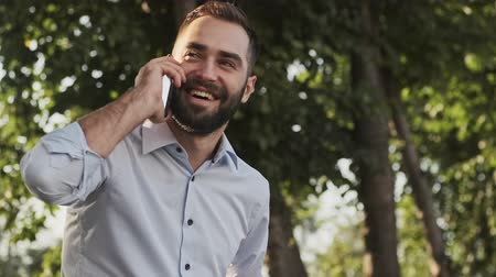 formální zahrada : Happy bearded businessman answering the call and talking by smartphone while sitting in park outdoors