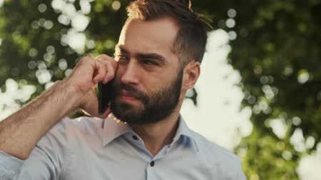 yöneticiler : Close up view of calm bearded businessman answering the call and becoming unhappy while sitting in park outdoors