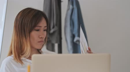 прическа : Concentrated asian business woman working with documents while sitting by the table in the office