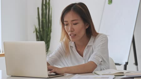 empregador : Upset asian business woman touching her head while working with a laptop in the white office Stock Footage