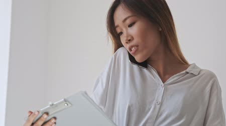 empregador : Concentrated asian business woman looking to a folder tablet with documents while having a phone call in the office Stock Footage